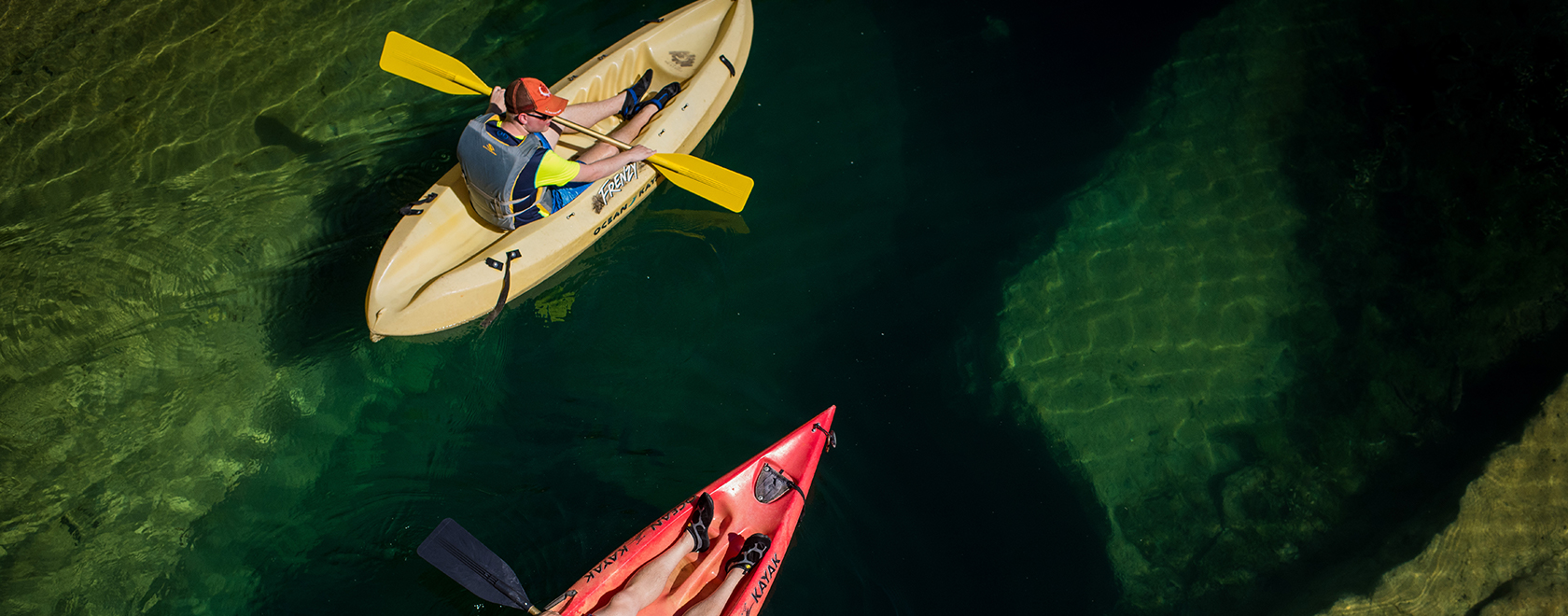 Overhead shot of two people on canoes