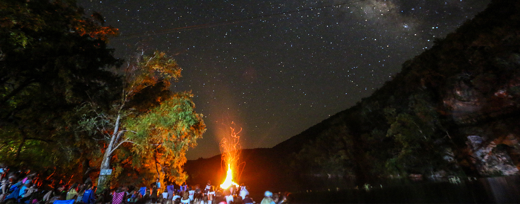 Night photo of a crowd overlooking a bonfire